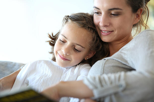 Mom with little girl reading book in sofa
